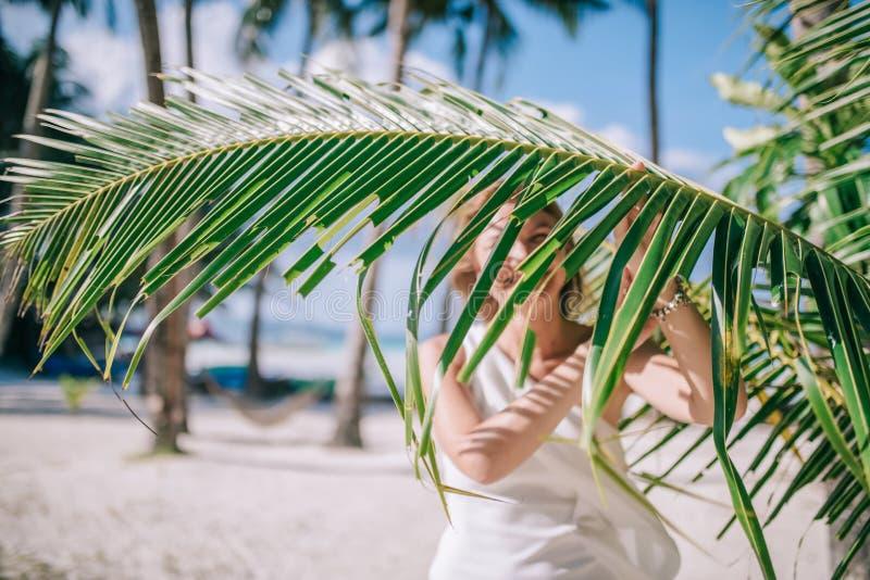 Portrait de longue fille heureuse de cheveux avec la robe blanche de port de bronzage étonnant près du congé vert gentil de paume photo libre de droits