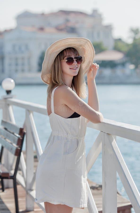 Portrait de longueur de trois-quarts de femme blonde aux cheveux longs dans le chapeau image libre de droits