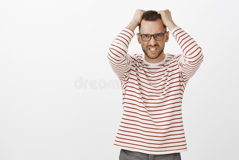Portrait de mâle barbu beau contrarié fâché en verres, tirant des cheveux hors de la tête et grimaçant de l'outrage image libre de droits