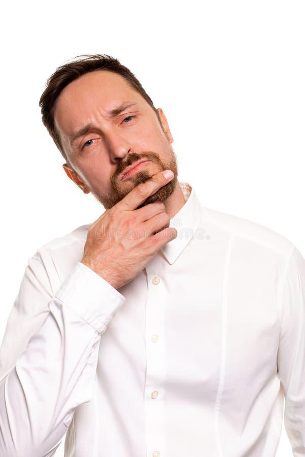 Portrait de mâle européen déterminé malheureux avec le menton émouvant de poil tout en pensant et regardant avec sérieux et photos libres de droits