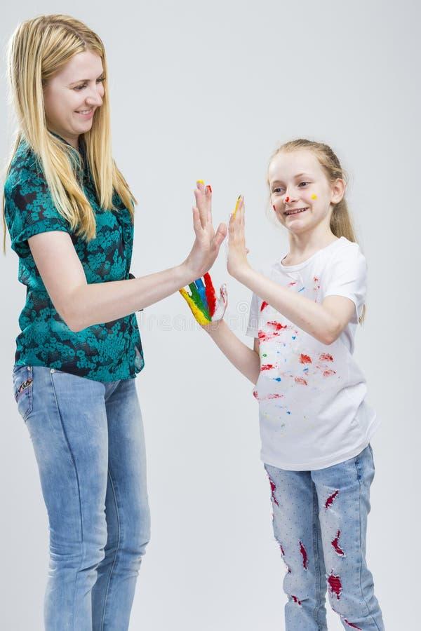 Portrait de mère et sa petite fille blonde caucasienne ayant le temps de peinture de main et de visage ensemble photos stock