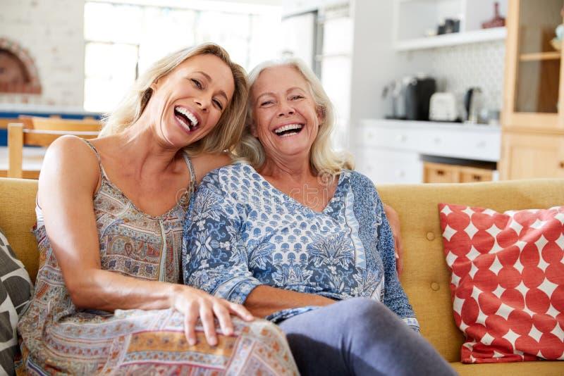 Portrait de mère de sourire avec la fille adulte détendant sur Sofa At Home image libre de droits