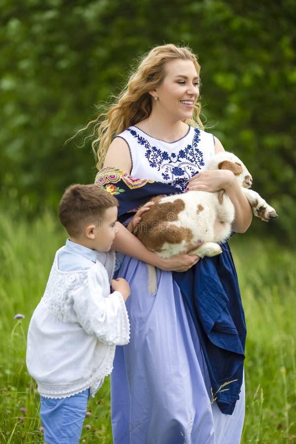 Portrait de mère de sourire avec son petit fils Tenir CUB d'extérieur nouveau-né d'agneau sur le fond de nature photographie stock