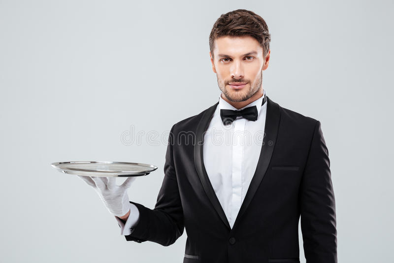 Portrait de maître d'hôtel dans le smoking tenant le plateau vide images stock