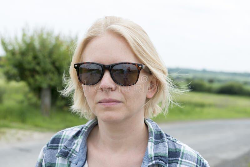 Portrait de Madame dans des lunettes de soleil dans l'extérieur photos stock