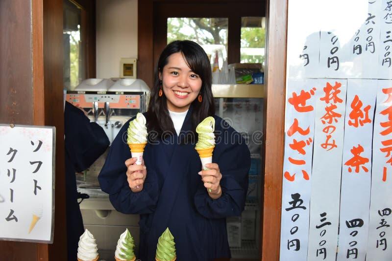 Portrait de main de femme tenant une crème glacée de matcha de thé vert dans le cône photo libre de droits