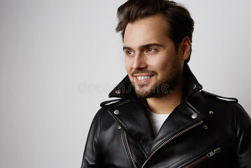 Portrait de mannequin beau de sourire dans la veste en cuir se reposant tout en se tenant sur le fond blanc horizontal image libre de droits