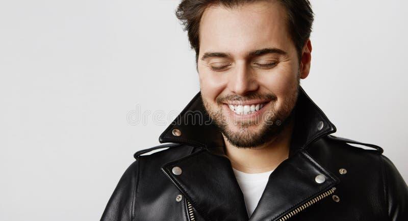 Portrait de mannequin de sourire dans la veste en cuir se reposant tout en se tenant sur le fond blanc horizontal images libres de droits