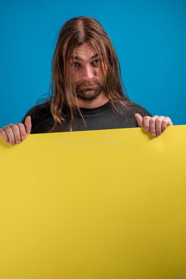 Portrait de masculin montrant un visage sérieux tout en tenant une bannière jaune photographie stock