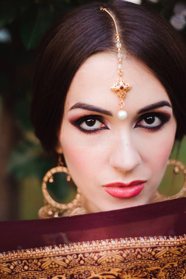 Portrait de modèle indien de beauté avec le maquillage lumineux qui cachant son visage derrière le voile Jeune femme indoue avec  image stock