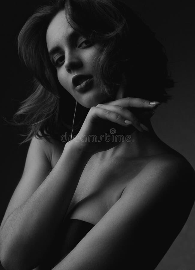 Portrait de modèle magnifique de brune avec les cheveux bouclés et beau le maquillage posant avec la lumière de contraste Rebecca images stock