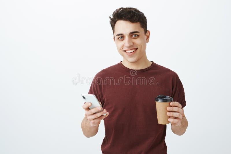 Portrait de modèle masculin beau insouciant dans le T-shirt rouge, café potable et smartphone de se tenir, faisant des affaires t images libres de droits