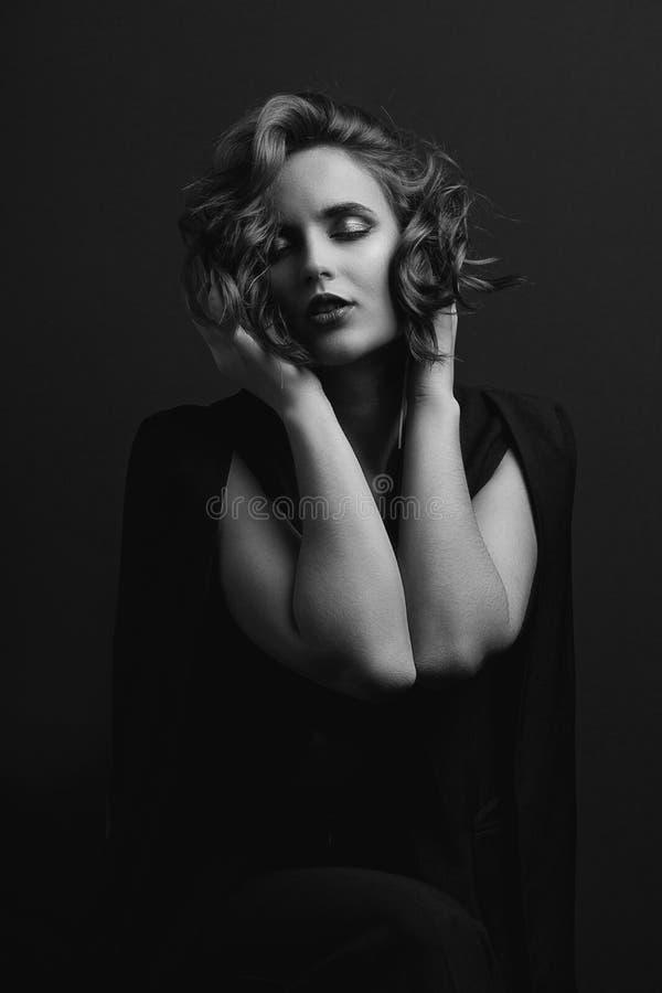 Portrait de modèle sensuel de brune avec des cheveux de vague posant avec la lumière de contraste Tonalité noire et blanche images libres de droits