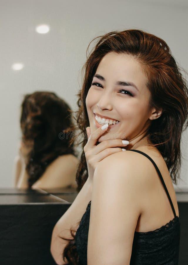 Portrait de mode de beauté de jeune femme asiatique de sourire sensuelle avec de longs cheveux foncés devant le miroir photos libres de droits