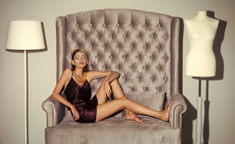 Portrait de mode de beauté Repos de fille sur le sofa gris au simulacre et au lampadaire photos stock