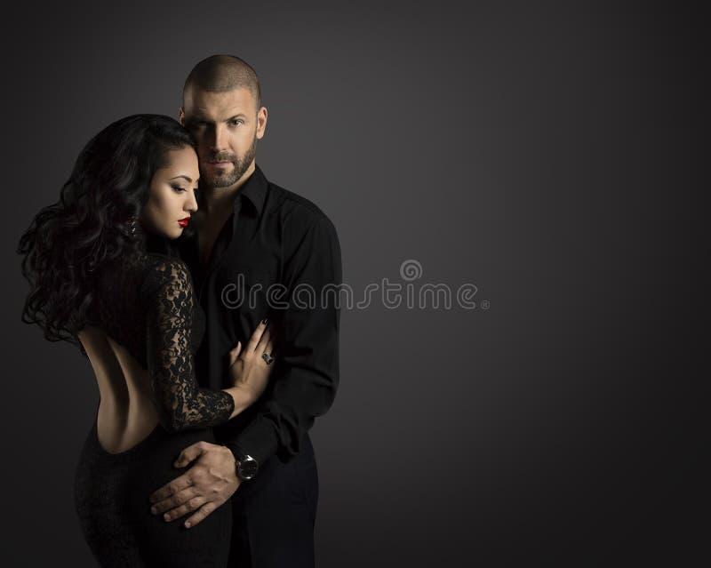 Portrait de mode de couples, femme d'étreinte de jeune homme dans le noir photos libres de droits