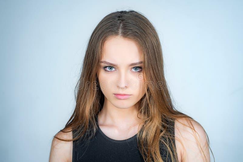 Portrait de mode d'une belle jeune femme posant au-dessus du fond blanc Fermez-vous vers le haut de la verticale d'un beau jeune  photo libre de droits