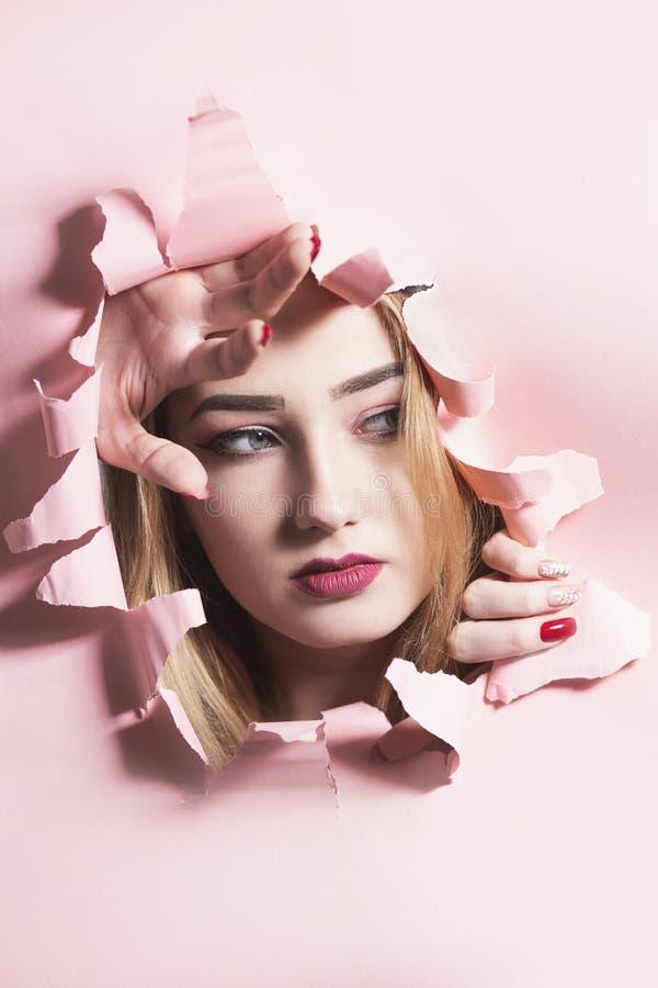 Portrait de mode d'une jeune femme d?chirant un trou en papier rose de carton, visage d'une fille avec le maquillage, libert? cr? image stock