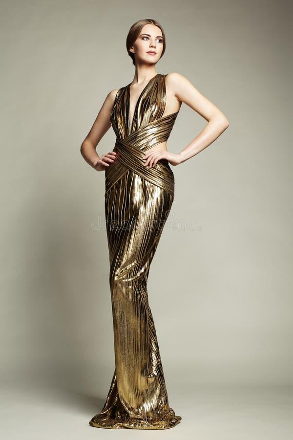 Portrait de mode de jeune belle femme dans la robe d'or photographie stock libre de droits