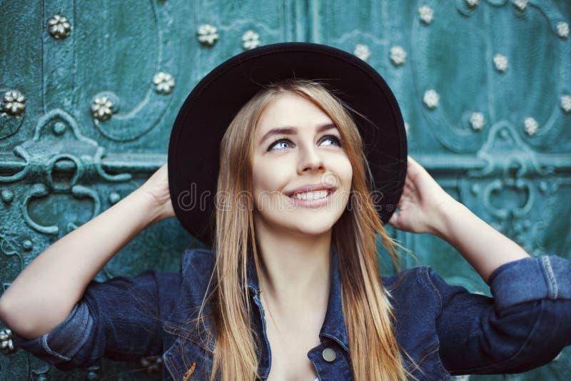 Portrait de mode de rue d'une belle jeune dame souriant et recherchant Chapeau à large bord élégant de port modèle Ville photo libre de droits