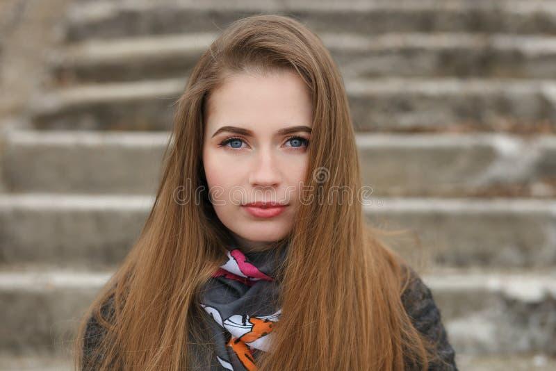 Portrait de mode de vie de jeune et jolie femme adulte avec de longs cheveux magnifiques posant en parc de ville avec la profonde photo libre de droits
