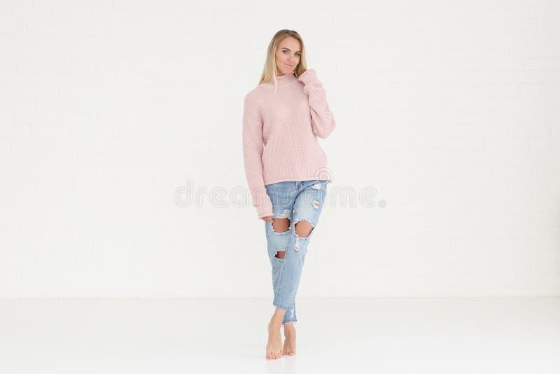 Portrait de mode de femme dans le chandail rose et des jeans déchirés photo libre de droits