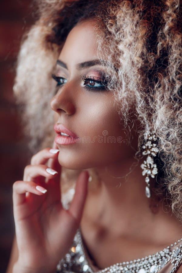 Portrait de mode de jeune belle femme afro-américaine avec des bijoux et le maquillage de égaliser photo stock