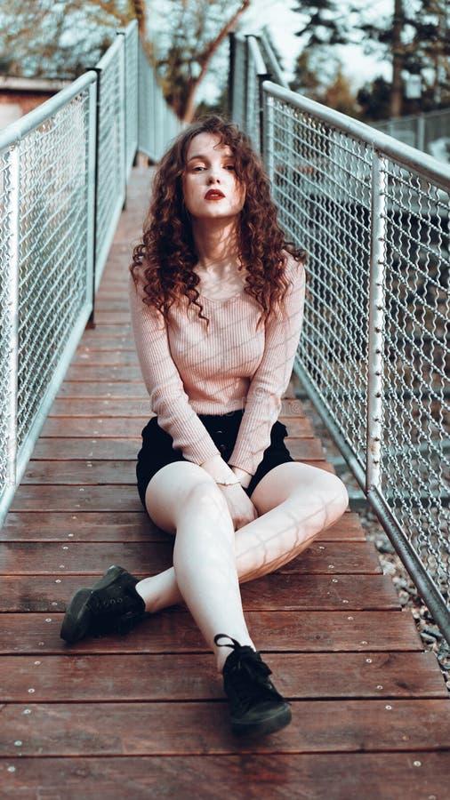 Portrait de mode de jeune femme à la mode se reposant près du rabitz de maillage photographie stock