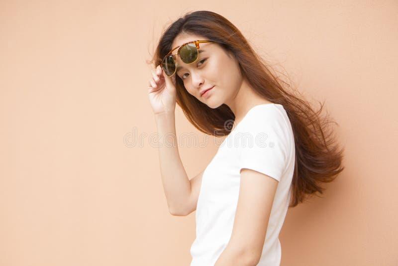 Portrait de mode de jeune femme utilisant des lunettes de soleil image libre de droits