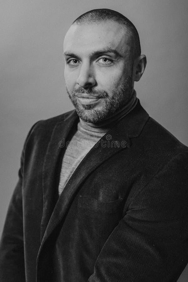 Portrait de mode de studio dans le monochrome Le jeune homme sérieux bel élégant a ouvert sa veste photos stock