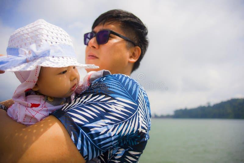 Portrait de mode de vie d'extérieur de jeune homme chinois asiatique heureux et fier en tant que père aimant tenant le bébé adora image libre de droits