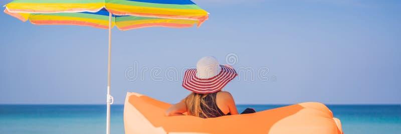 Portrait de mode de vie d'?t? de jolie fille se reposant sur le sofa gonflable orange sur la plage de l'?le tropicale D?tente photo libre de droits