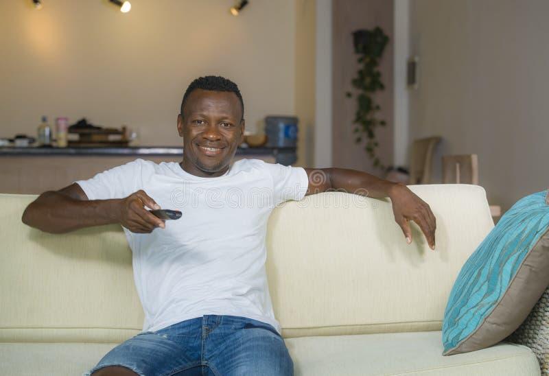 Portrait de mode de vie du jeune homme américain d'africain noir attirant et heureux tenant le film de observation de télévision  photographie stock