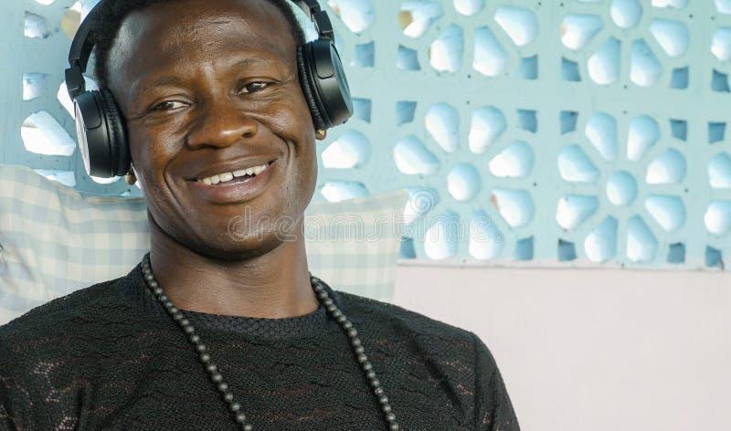 Portrait de mode de vie de jeune écouter gai de sourire d'homme afro-américain noir frais attirant et heureux la musique sur le j images stock