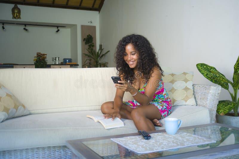 Portrait de mode de vie de jeune femme américaine d'africain noir heureux et bel à la maison utilisant la mise en réseau de télép photographie stock libre de droits