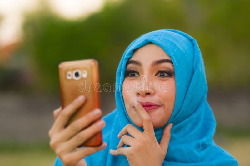 Portrait de mode de vie de jeune femme de touristes heureuse et belle dans l'écharpe musulmane de tête de hijab prenant la photo  images stock
