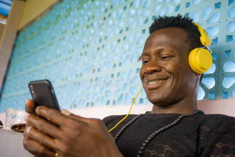 Portrait de mode de vie de jeune homme afro-américain de noir frais attrayant et heureux de hippie utilisant la mise en réseau de photographie stock