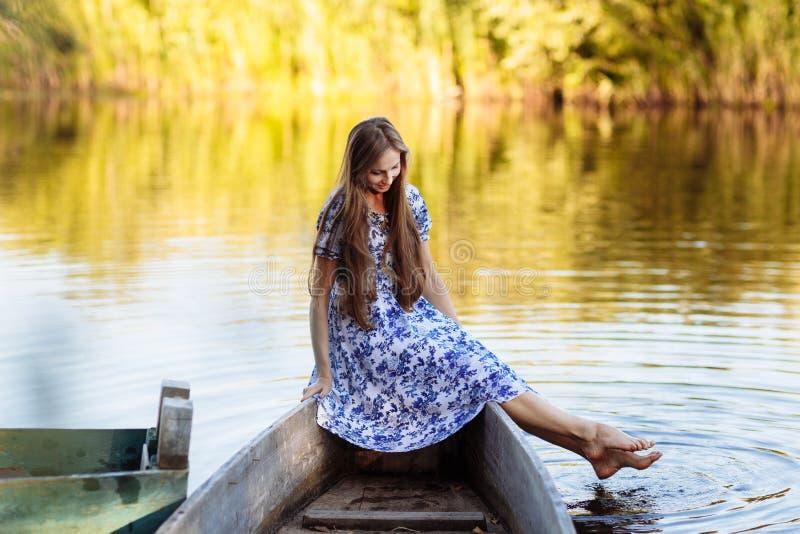 Portrait de mode de vie de la jeune belle femme s'asseyant au canot automobile fille ayant l'amusement au bateau sur l'eau image libre de droits