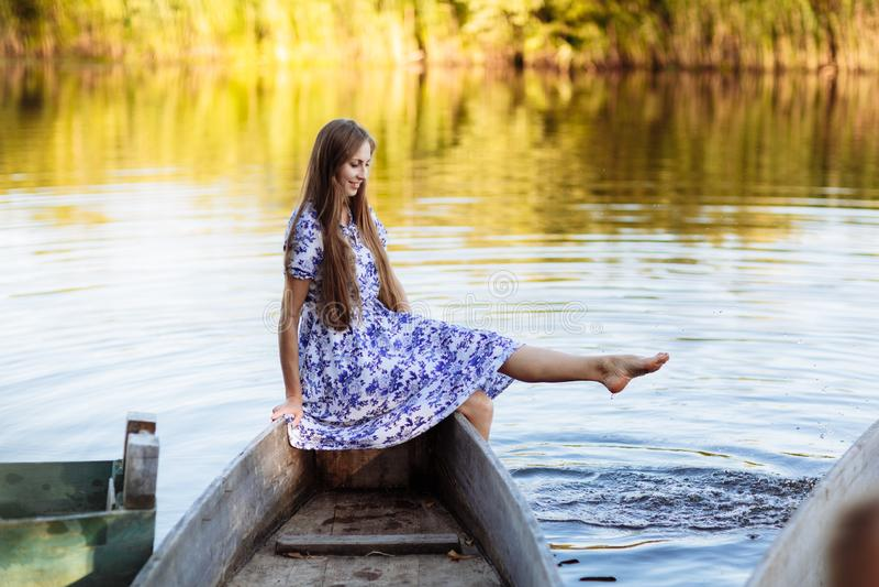 Portrait de mode de vie de la jeune belle femme s'asseyant au canot automobile fille ayant l'amusement au bateau sur l'eau photographie stock libre de droits