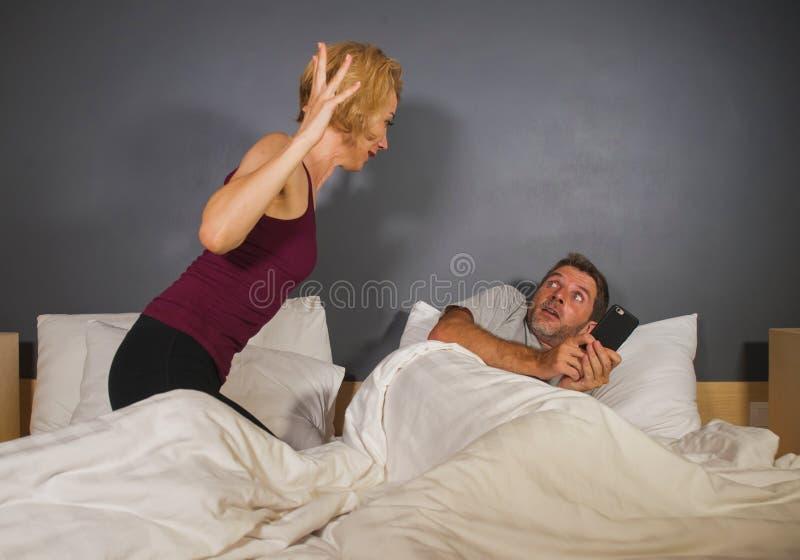Portrait de mode de vie de mari ou d'ami à l'aide du téléphone portable dans le lit avec sentiment frustrant fâché d'épouse ou d' image libre de droits