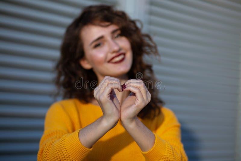 Portrait de mode de vie : modèle gai de brune avec les cheveux bouclés dans y photo stock