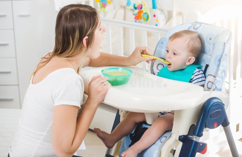 Portrait de 10 mois de bébé garçon s'asseyant en highchair et gruau eatting de cuillère image libre de droits