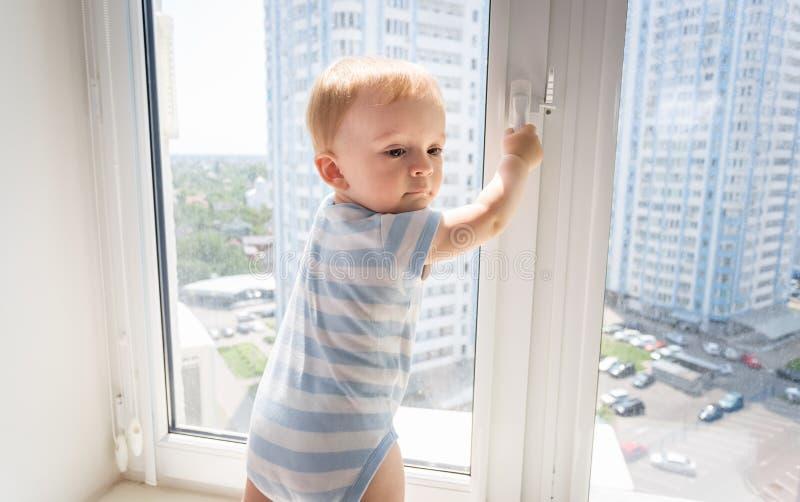 Portrait de 10 mois de bébé essayant à la fenêtre ouverte image stock