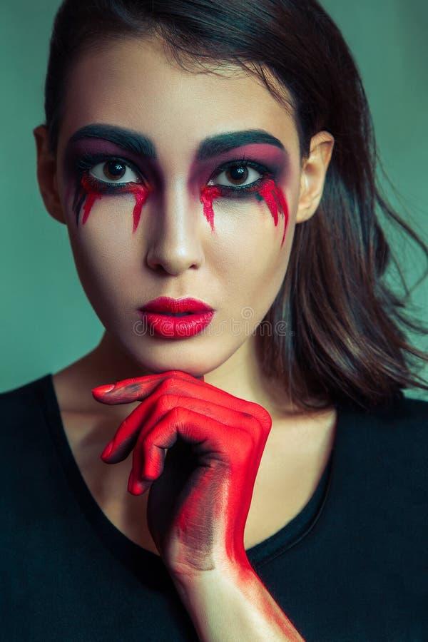 Portrait de monstre anormal avec le maquillage coloré sale de désordre sur son visage femme pleurante avec les larmes et la main  photos stock