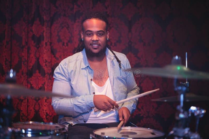 Portrait de musicien de sourire jouant le kit de tambour image stock