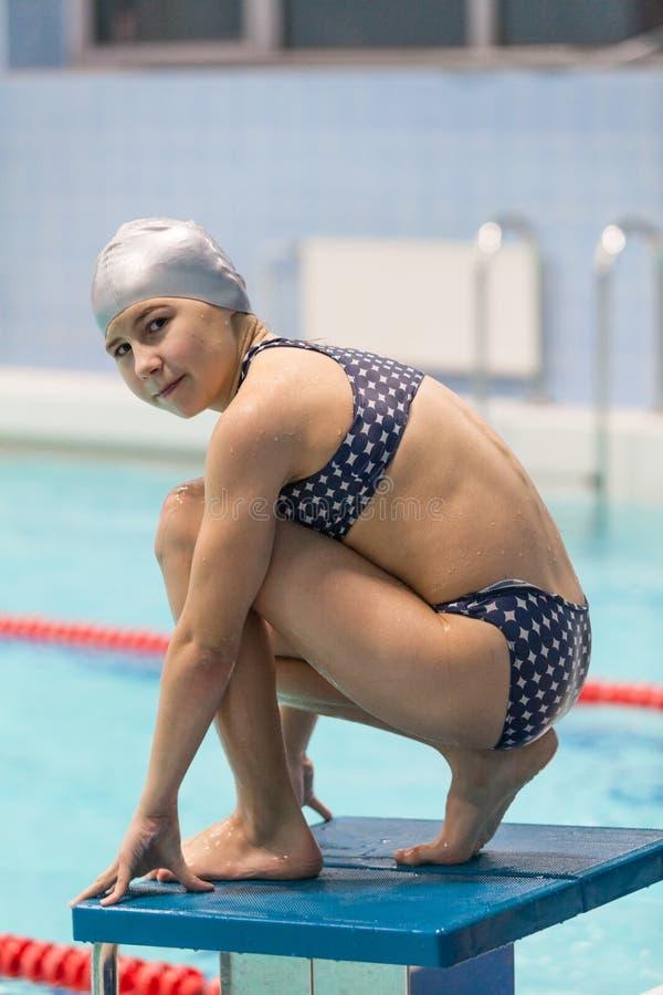Portrait de nageuse de jeune fille sur le bloc commençant prêt à sauter dans la piscine Gosse sportif photos libres de droits
