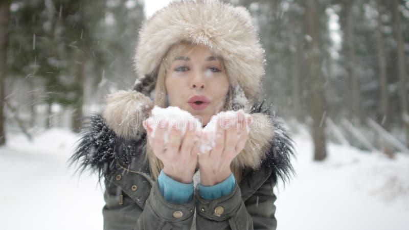 Portrait de neige de soufflement de sourire de femme à un appareil-photo photos stock