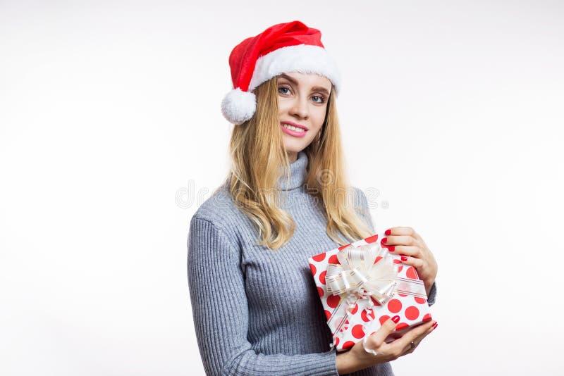 Portrait de Noël d'une belle femme blonde dans le chapeau de Santa et des boîtes rouges de se tenir avec un cadeau sur un fond bl photo stock