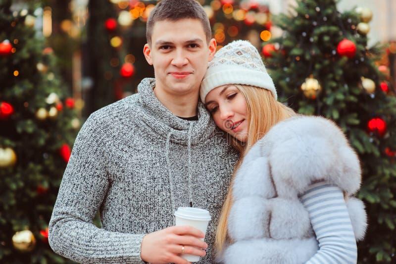 portrait de Noël des ajouter heureux au vin chaud ou au thé chaud marchant sur des rues de ville décorées pendant des vacances photographie stock libre de droits