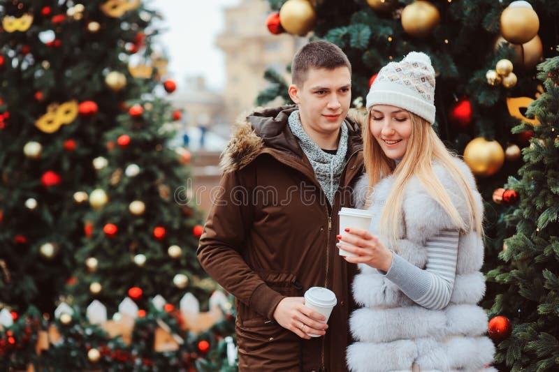 portrait de Noël des ajouter heureux au vin chaud ou au thé chaud marchant sur des rues de ville décorées pendant des vacances photos stock